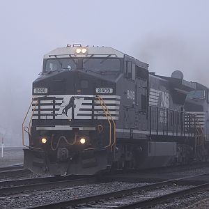 Still in the fog NS 8409 heads east passed the depot in Elkhart